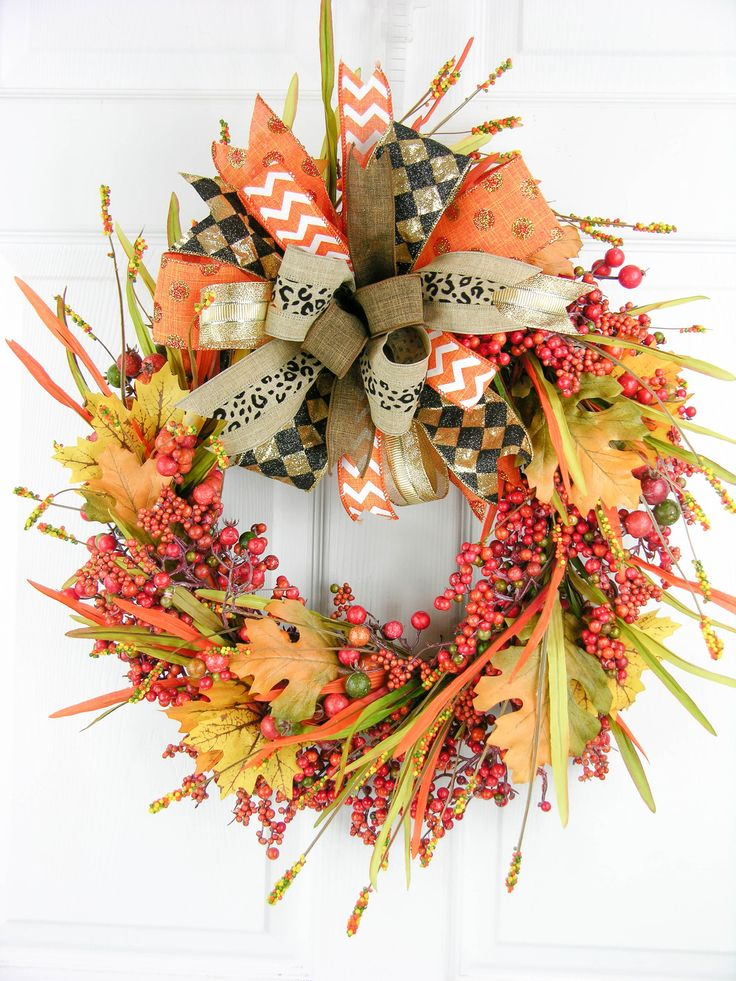 """A six patterned Terri Bow with animal accented ribbon is center stage with this design. The wreath is full of fall berries in all the colors of the season, leaves and grassy stems. Measures 24""""H X 20"""""""