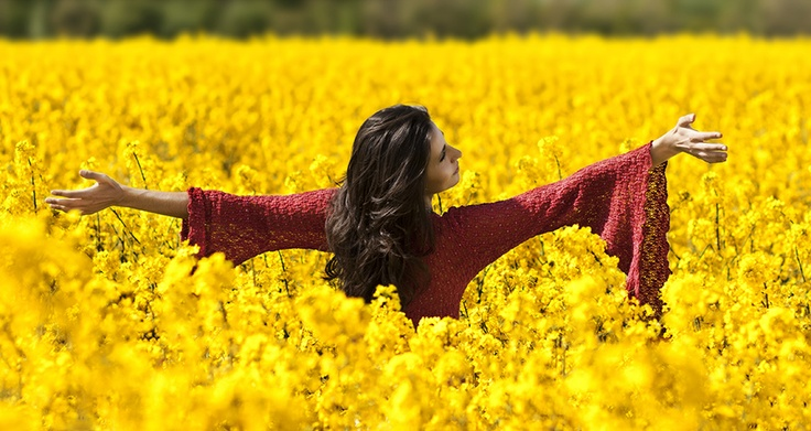 Beautiful red dress woman in canola field