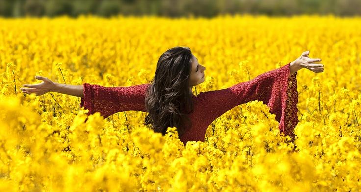 Beautiful red dress woman in canola field