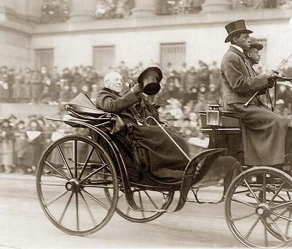 Woodrow Wilson waving top hat to crowd from open carriage during Armistice Day procession for Unknown Soldier burial.