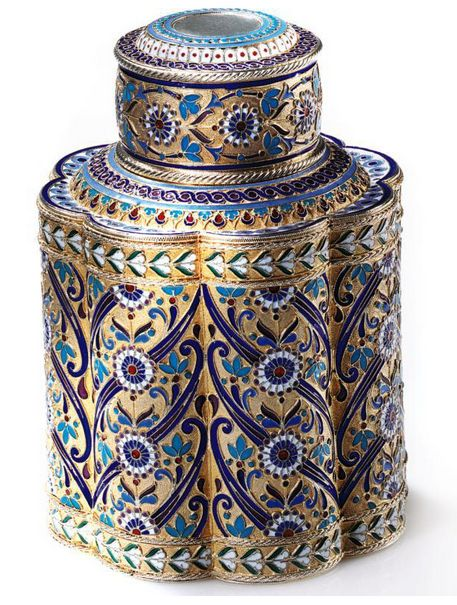 A Russian gilded silver and enamel tea caddy, Antip Kuzmichev, Moscow, 1892. Of octagonal section with lobed sides, enameled with colorful stylized foliage on a gilded stippled ground, with slip-on cover and with interior cork and gilded silver stopper, the base inscribed 'Made for Tiffany & Co.'