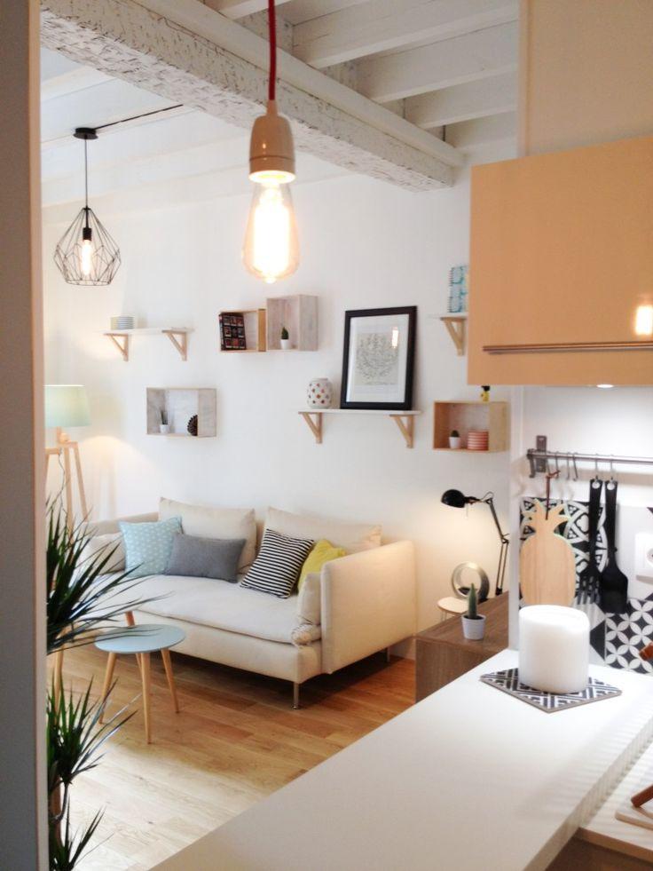 Salon scandinave, touches pastel, table d'appoint scandinave et lampe fileuse. On apprécie beaucoup le cachet apporté par les poutres apparentes.