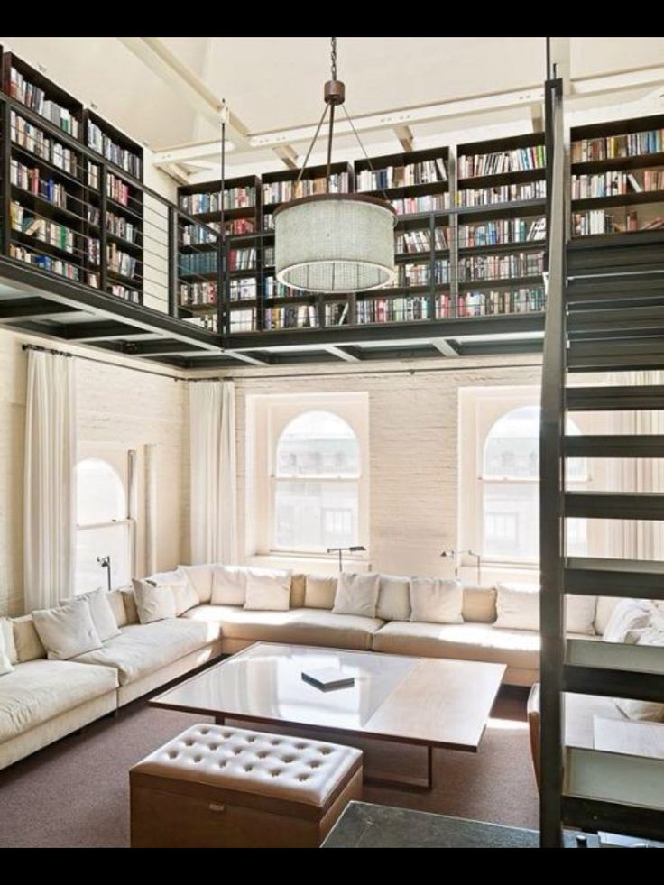 Book lovers understand the challenge of storing their books without taking on the appearance of a hoarder.. This upper #library solves the issue, offsetting the minimalist living room with a wooden #loft paired with dark green #shelves, and stairs.