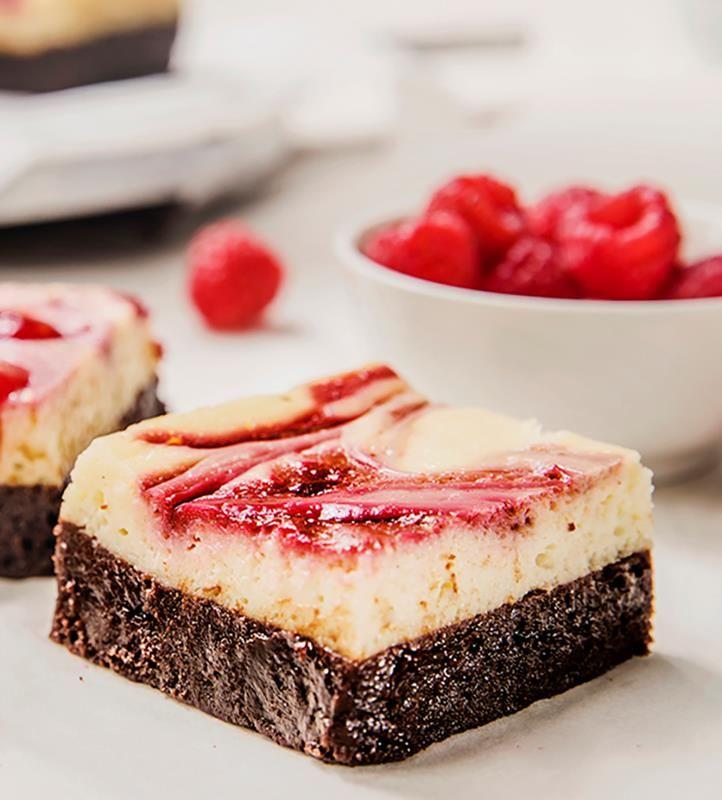 Ostekake og brownies i en og samme kake? En genial match! Brownies i bunn, kremen til ostekake oppå og en dæsj bringebærsaus på toppen.