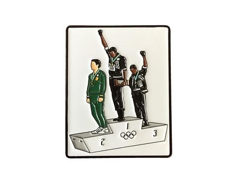 Lapel pin of 3 men standing on an olympic podium at the 1968 olympics. Two of the men have their fists raised in a Black power salute