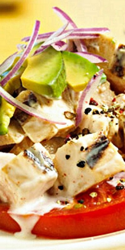 Margarita-Grilled Chicken Salad - Creamy avocado, red onion, and grilled chicken marinated in margarita mix, cumin, and lime peel tops juicy tomato slices.