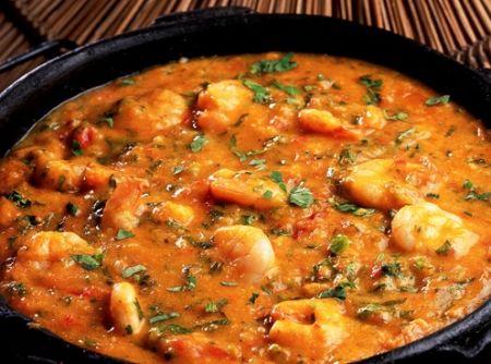 Receita de Bobó de Camarão - 1 kg de camarão com casca e com cabeça, 1 litro de água, 500 g de mandioca (aipim), 1 cebola média (100 g), picada, 2 colheres (sopa) de óleo, 2 tomates médios (240 g), sem pele e sem sementes, picados, 1 colher (chá) de sal ou a gosto, 1 pitada de pimenta-do-reino, 1 colher (sopa) de coentro picado, 1/2 xícara de leite de coco (120 ml), 2 colheres (sopa) de azeite-de-dendê, 1 pimenta-malagueta ou dedo-de-moça picada, folhas de salsinha ou coentro (para decorar)