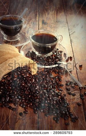 Cups of aromatic coffee on wooden table.