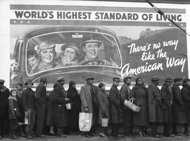 """Il difficile rapporto tra rappresentazione e realtà.  (Uomini e donne neri in coda per ricevere vestiti e cibo dopo la piena del fiume 'Ohio. Dietro di loro giganteggia un poster con l'immagine della famiglia felice americana standard di quegli anni: madre, padre, figlio maschio e figlia femmina bianchi sorridenti e biondi. Il poster dice """"Il tenore di vita più alto del mondo"""". Louisville, nel Kentucky, 1937)  Ph. Margaret Bourke"""