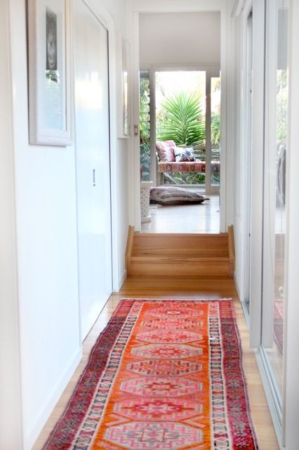 Small corridor decorated with colorful rug for boho vibe