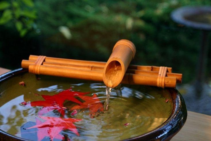 idée déco avec une fontaine en bambou et feuilles rouges