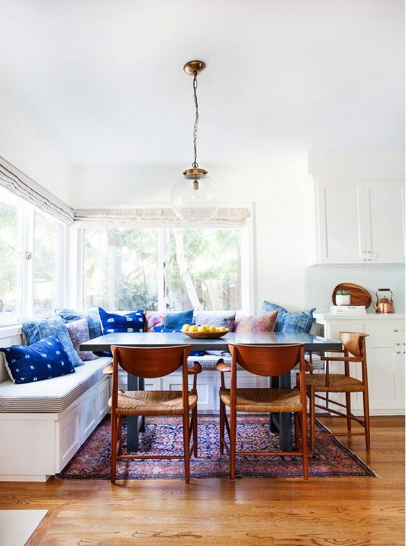 Breakfast nook with indigo Shibori dyed pillows and woven midcentury dining chairs.: