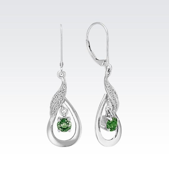 This set of earrings, crafted of quality sterling silver, is the perfect amount of glimmer and color to add to any wardrobe. The attractive set features two round green sapphires (approx. .68 carat TW) dangling within the design while 28 round pavé-set diamonds (approx. .14 carat TW) swirl above. The earrings dangle at one and one quarter inch in length from a french wire backing and have a total gem weight of approximately .82 carat.
