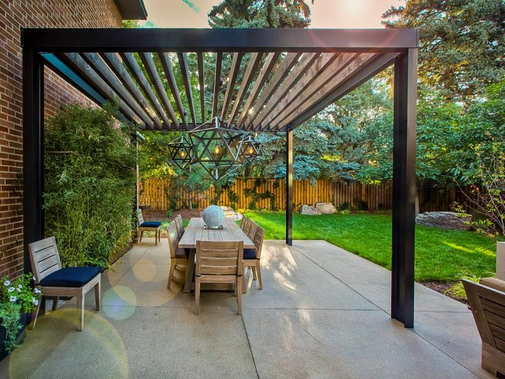 This cozy outdoor space features a custom-designed pergola. The pergola uses steel I-beams and Douglas fir joists to cover an outdoor dining area.