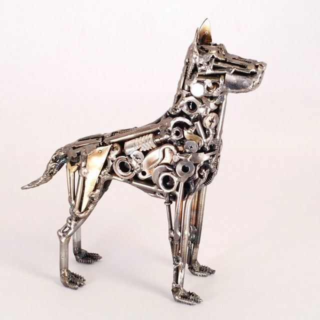 A modern sculpture of a dog it uses metal objects to for Dog wire art