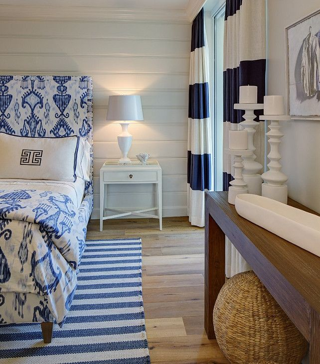 Beach house bedroom. Blue and white bedroom. Coastal decor. Nautical bedroom. Striped Area Rug. Striped drapes, Blue and white stripes, upholstered headboard, wood walls. Beadboard bedroom wall. Wooden table. W Design Interiors.