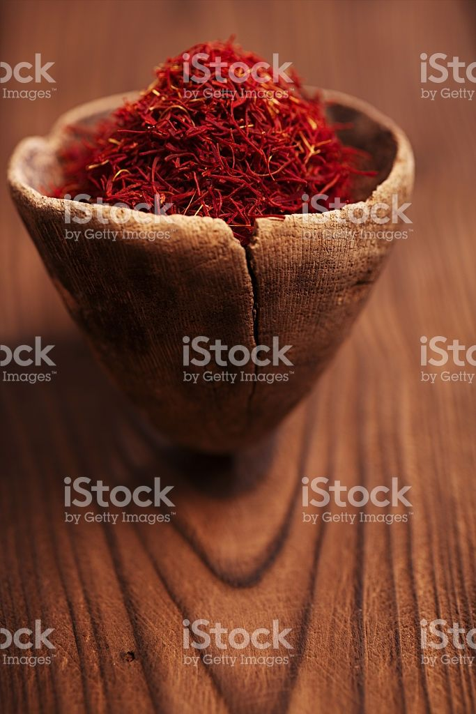 saffron spice in antique wooden spoon on old wood background royalty-free stock photo
