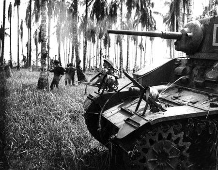 The Battle of Buna-Gona saw Australian and Allied forces attack several cities in New Guinea captured by Japanese forces. On January 7th 1943, battalions like the one seen here (the 2/6th Armoured Regiment) were part of the successful final assault on Buna. This picture, taken during live battle, shows the machine guns on the front of the tanks pointed upward to shoot down snipers in the trees. This particular machine gun shot 10,000 rounds that day.