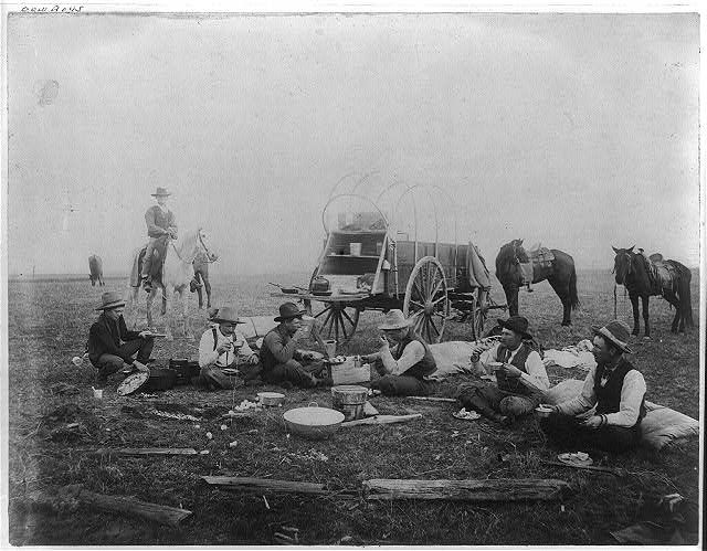 Cowboys eating out on the range, chuck wagon in background - I've been told that Charles Goodnight came up with the idea for the first chuckwagon, and had it outfitted at a blacksmith shop on York   Avenue in Weatherford, Texas.