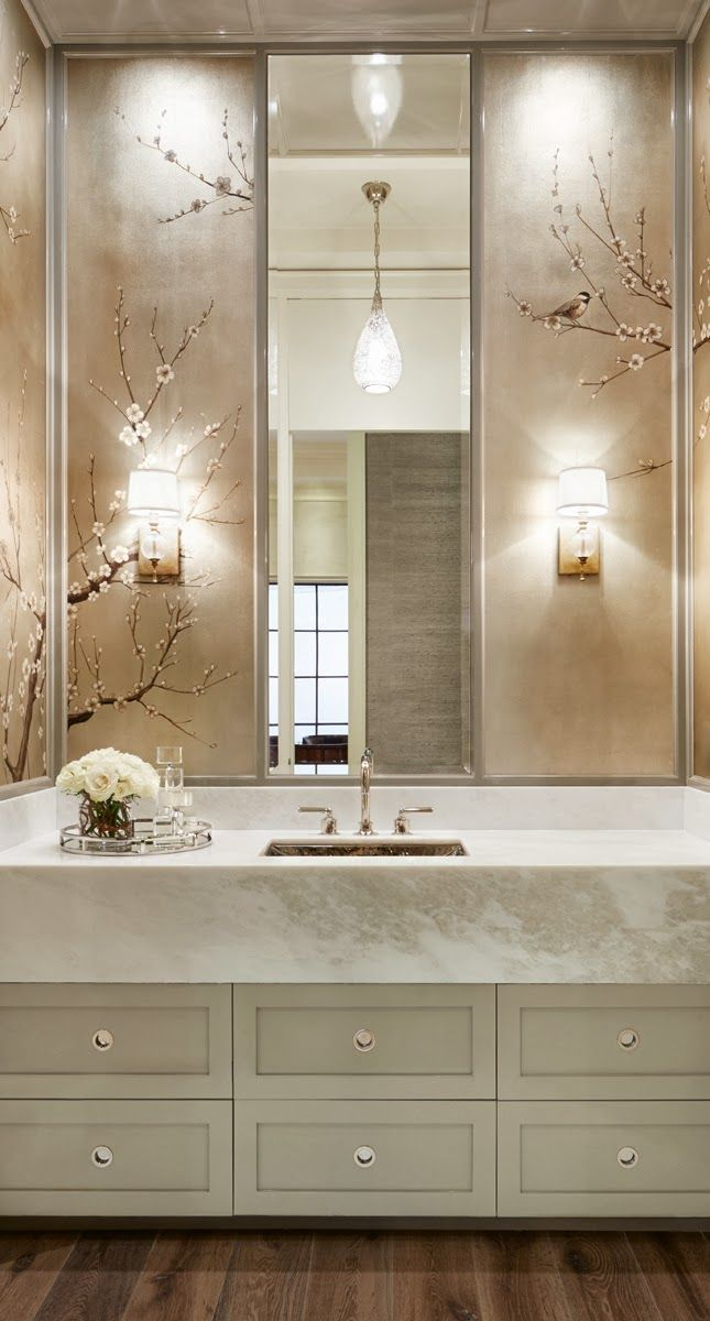 cherry blossom muraled panels paired with fat apron front marble counter, wood floors, gray cabinetry.