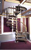 """(Above) 5' 0"""" Diameter Victorian One Cast Aluminum Kit with optional 1-1/4"""" brass handrail with polished brass scroll handrail ends, double in-between spindles, scroll design tread ends, and """"antique"""" gold leaf bronze baked finish.(Above Right)View of upper level showing optional curved well railing with polished brass tops and extra posts with finials."""