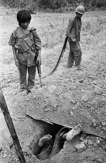 February 1974, Cambodia -- Young Cambodian government soldiers observe the dead body of a Khmer Rouge soldier. --- Image by © Patrick Chauvel/Sygma/Corbis