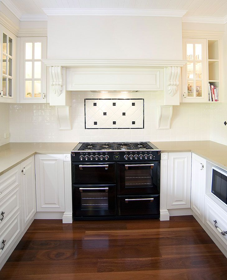 A big upright stove under a mantlepiece.  This kitchen is full of old world charm