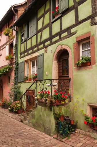 Half-Timbered House in Riquewihr / Alsace / Haut-Rhin, France. Riquewihr is one of the most famous villages in the region, and probably the most visited. Its location among the vineyards gives it a charm. The village of course has numerous timbered houses, beautifully highlighted and flowers, and the ramparts, well preserved, surround this pearl of the vineyard.