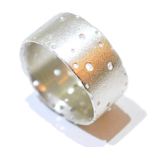 A beautiful sterling silver ring with a satin finish features an uneven textured edging which creates an organic structural quality that radiates professional handmade design. The drilled holes look natural and mimicked from nature, the ring has subtle details which make it perfect for everyday wear or to jazz up an outfit.
