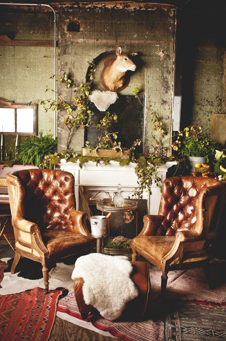 These are our Single Malt leather wingback chairs with a burlap backing exposing the bones in the backs of the chairs. We decked them out using our Kilim rugs, some shearling throws and one of our trusty bar carts to create a nice masculine mantle hang. We had to throw in a pear tree + ferns to bring it to life! | Patina
