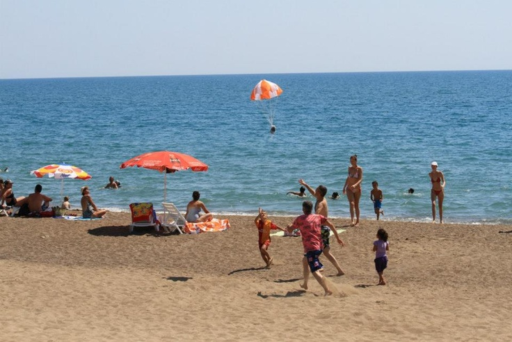 Üzerinde Antalya Migros Alışveriş Merkezi logosu bulunan Paramotor aracılığıyla havadan paraşütlere bağlanmış sürpriz hediyeler tatilcilerin üzerine bırakıldı.