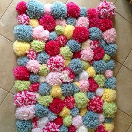 TAPIS DE POMPONS Pour le pied de lit, pour la salle de bain ou devant le foyer, ce tapis de pompons fera sensation. Créez des pompons en laine et ensuite assemblez-le sur un tapis quadrillé en plastique (que vous trouverez dans les magasins d'artisanat. Alternative : Prenez des languettes de tissus de différentes couleurs et formez des nœuds simples à travers les trous du tapis.