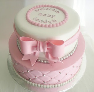 """Quilted Pink and White Baby Shower Cake! This cake was ordered for a couple celebrating the approaching birth of their baby girl, Londyn. They were unsure of what exactly they wanted, they just knew they didn't wanna play up any type of """"London, England"""" theme. So we choose a simple and sweet design that would make anyone say """"awww"""" :). French vanilla cake with cream cheese and fresh strawberry filling covered in fondant icing. 100% edible!"""