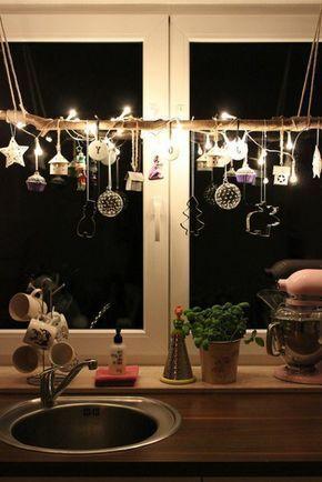Idee: Ast in Weihnachtsfenster mit Lichtern und Anhängern dekoriert (z.B. aus Bienenwachsplatten)