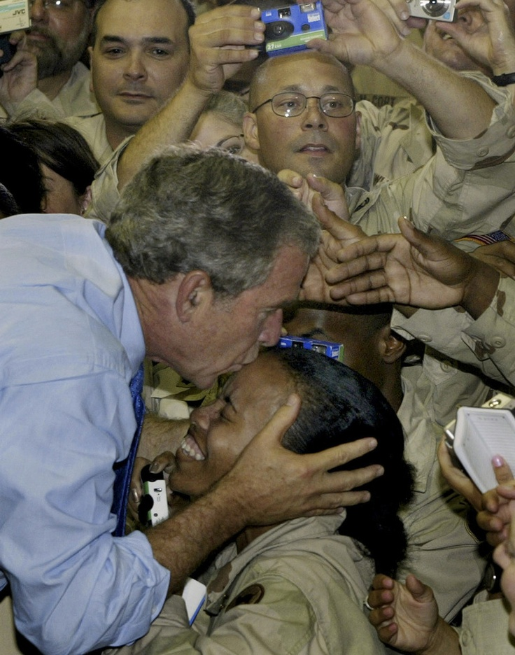 President George W. Bush kisses a soldier as he greets U.S. military personnel at As-Sayliyah base near Doha, Qatar, 2003.