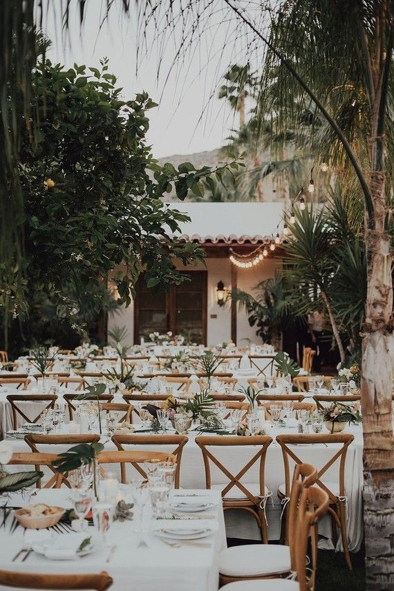 **LOVE THIS TABLE SETTING** White table cloths, tropical leaves in small clear vases with simple flowers as center pieces, lots of small white votive candles. *different chairs though*