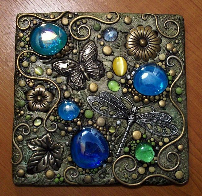 "Polymer clay on a 6"" square piece of treated hardboard. Included are brass butterfly, leaves and flowers, glass gems and a metal dragonfly. Painted with acrylic and metallic paint."