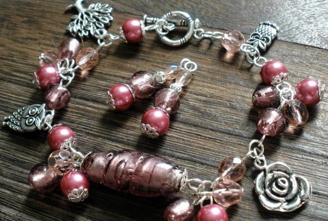 Stredový prvok tvorí krásna fialová vinutka, okolo ktorej cinkajú perly v sladkom fialovo-vintage odtieni, malé vinutky rovnaké ako stredový kúsok, brúsené ohňovky v lososovom odtieni a rozkošné prívesky dvoch rôznych sovičiek, ružičky a stromu.  Americké zapínanie pre lepšiu manipuláciu.  Náušničky z rovnakého materiálu.