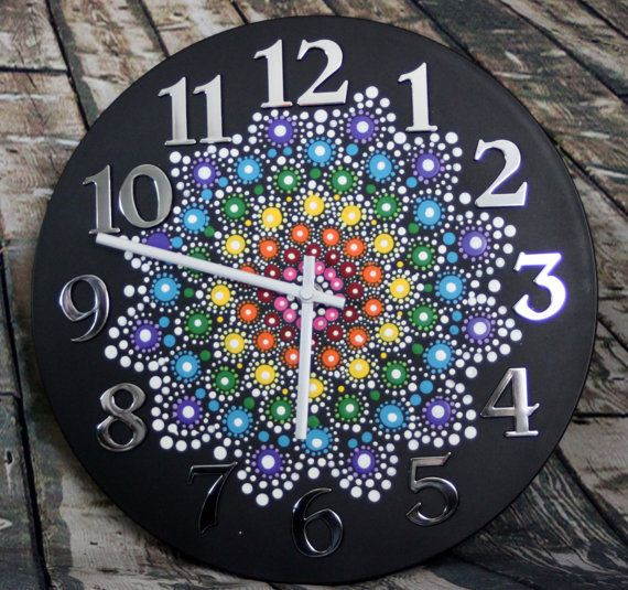 Art becomes functional with this clock. A stunning jewel drop mandala graces the front of the clock while silver numbers frame the mandala in the center. The black background provides a stark contrast so that the mandala jumps out at you. When you buy this clock, you buy a piece of art. Materials *Resin clock *Acrylic Paint  Measures 12 in diameter  This item is hand-made so it will have imperfections due to the process of making the mandala. You will receive the exact item in the…