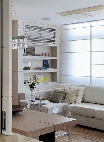 Na estante da sala, um painel ripado disfarça o aparelho de ar condicionado.