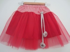 Red tutu girl's skirt with red polka dot wide waist and two handmade hanging flowers from a small loop. Sizes 2y-7y. Made in Melbourne