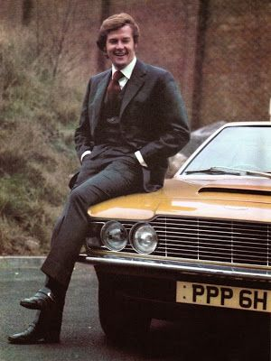 Roger Moore (Lord Brett Sinclair) on the hood of his Aston Martin DBS with original registration number (PPP 6H)