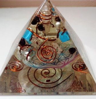 Orgone Pyramid with Paper desighn of seven chakra This is huge orgone Pyramid of base length 3.5inches.The base is a square.It uses natural crystals, resin , copper and aluminium powder and copper ring.It has high vibrations