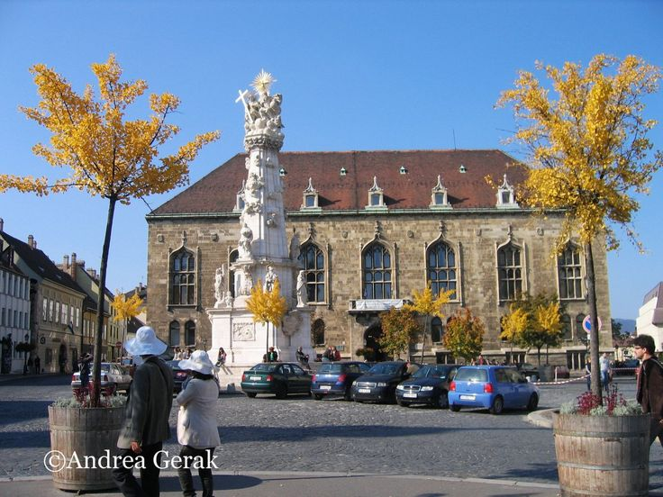 Trinity Square (Szentháromság tér) in Budapest, Hungary. Sunny afternoon with blue sky and yellow leaves on the trees, and the Baroque Trinity statue in the Buda Castle district. Two tourists in th...
