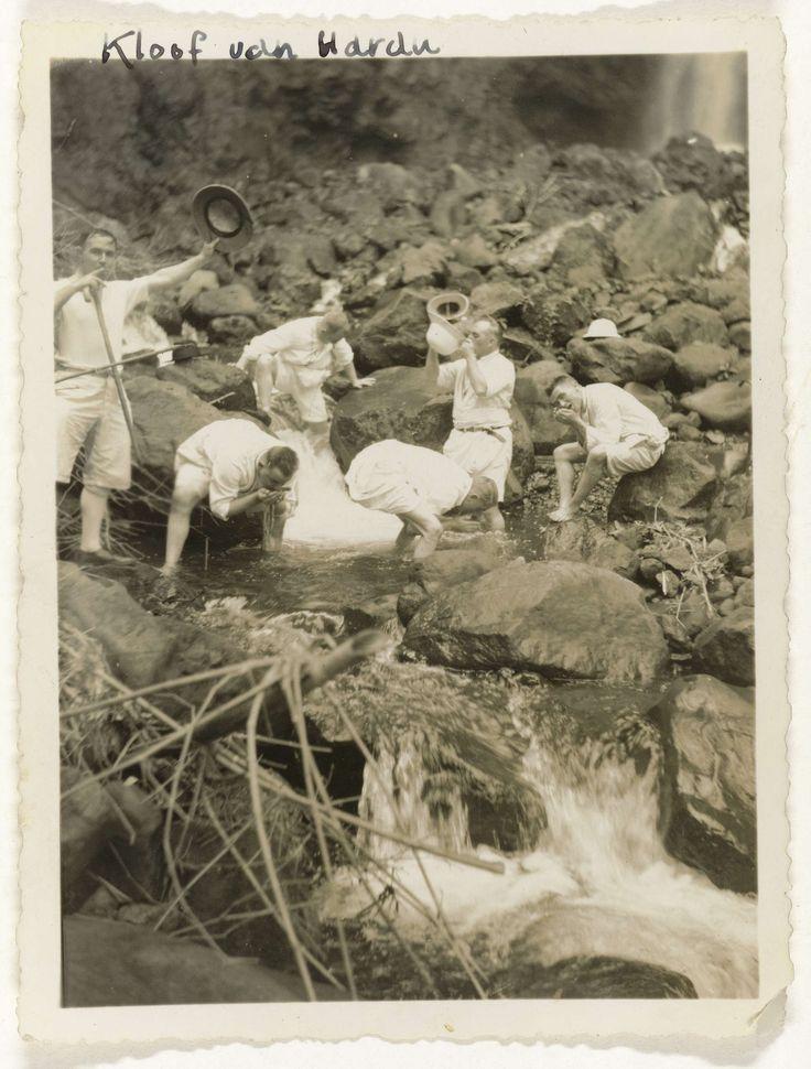 Anonymous | Kloof van Harau, Anonymous, 1930 - 1939 | Zes Fraters van Tilburg in korte broek, poseren hurkend en drinkend uit een stroom bij de waterval in de kloof van Harau op Sumatra. Losse foto afkomstig uit het losbladig fotoalbum over de Fraters van Tilburg op Celebes en Sumatra.