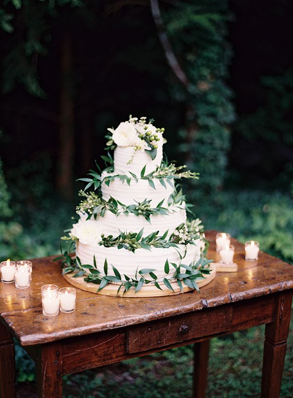 4 tier buttercream wedding cake with olive leaves and green foliage.  Photo by Clark Brewer