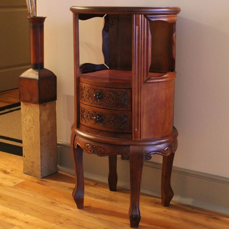 This wooden accent table makes a perfect bedroom nightstand, and it can also serve as a telephone or plant stand in your living room. Its intricate hand carvings give it a timeless, classic look, and it features two convenient front drawers.