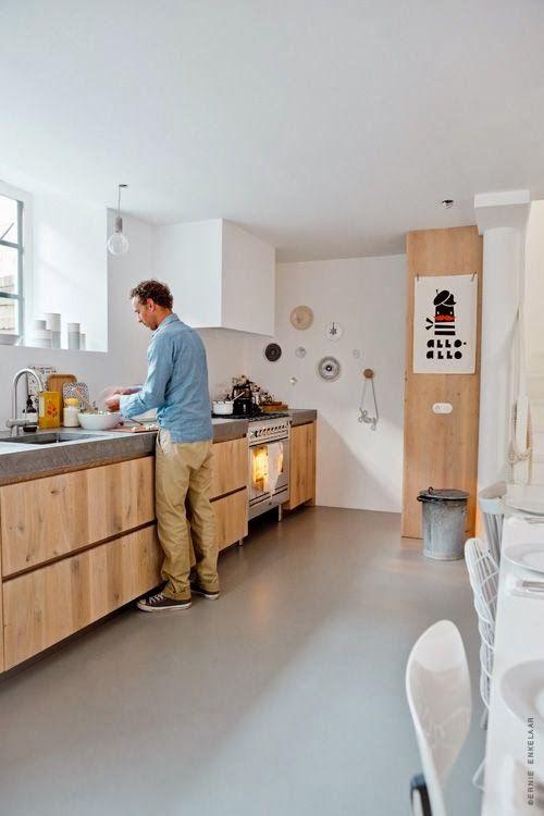 Jasnoszara podłoga żywiczna w strefie kuchennej - pięknie łączy się z drewnianymi frontami szafek.