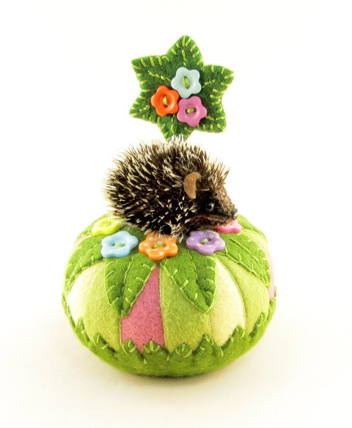 """I ❤ pincushions . . . A hand sewn hedgehog atop a wool felt pin cushion hand crafted in soft spring colors cupped inside of, & topped with hand appliqued leaves. Hedgie is hand sewn from tipped dense mohair fabric, & firmly stuffed with wool. His fur has been treated with a stiffening agent that gives him a real quilled effect. The face & ultra suede ears have been hand tinted to give him a sweet realistic character.  Hedgie measures 2"""" from nose to rear. Pincushion 3 1/2 by 2 ~By…"""