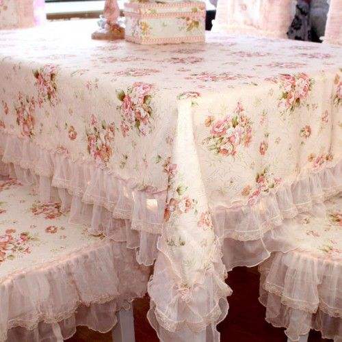 Lots of Shabby here. Pink roses & ruffles tablecloth & chairs.